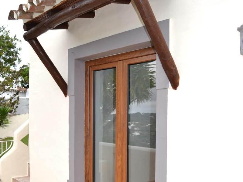 Détail porte-fenêtre oscillo-battante en PVC imitation bois chêne dorée