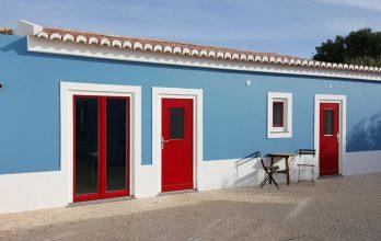 Maison avec menuiserie de fenêtres et portes extérieures en bois rouge et bleu