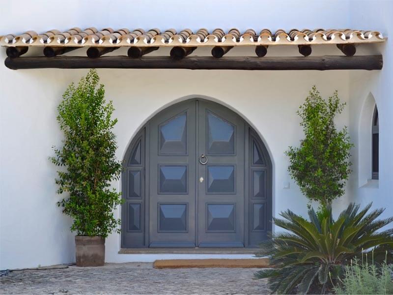 Porte d'entrée en bois grise avec des elements vitrées