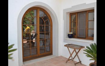 Porte-fenêtre en bois naturel cintrée