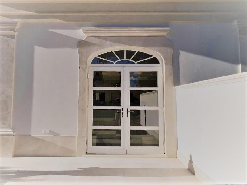Porte-fenêtre cintrée en bois blanc avec croisillons